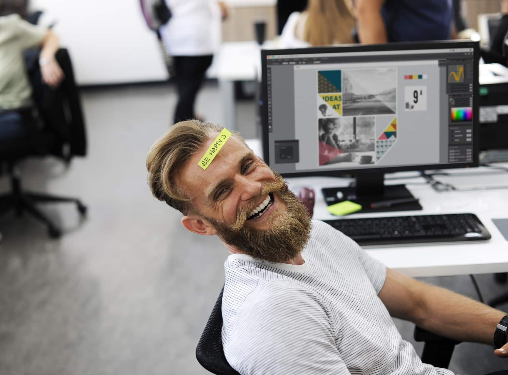 "Man with sticker on forehead saying ""be happy"" while working on a digital project in design software"