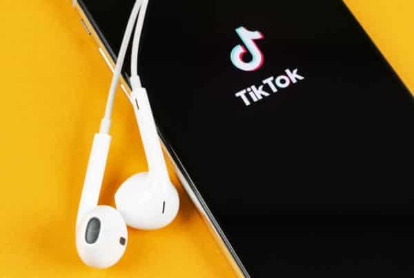 A yellow background and a black iPhone with the TikTok logo on it and earbuds plugged in.