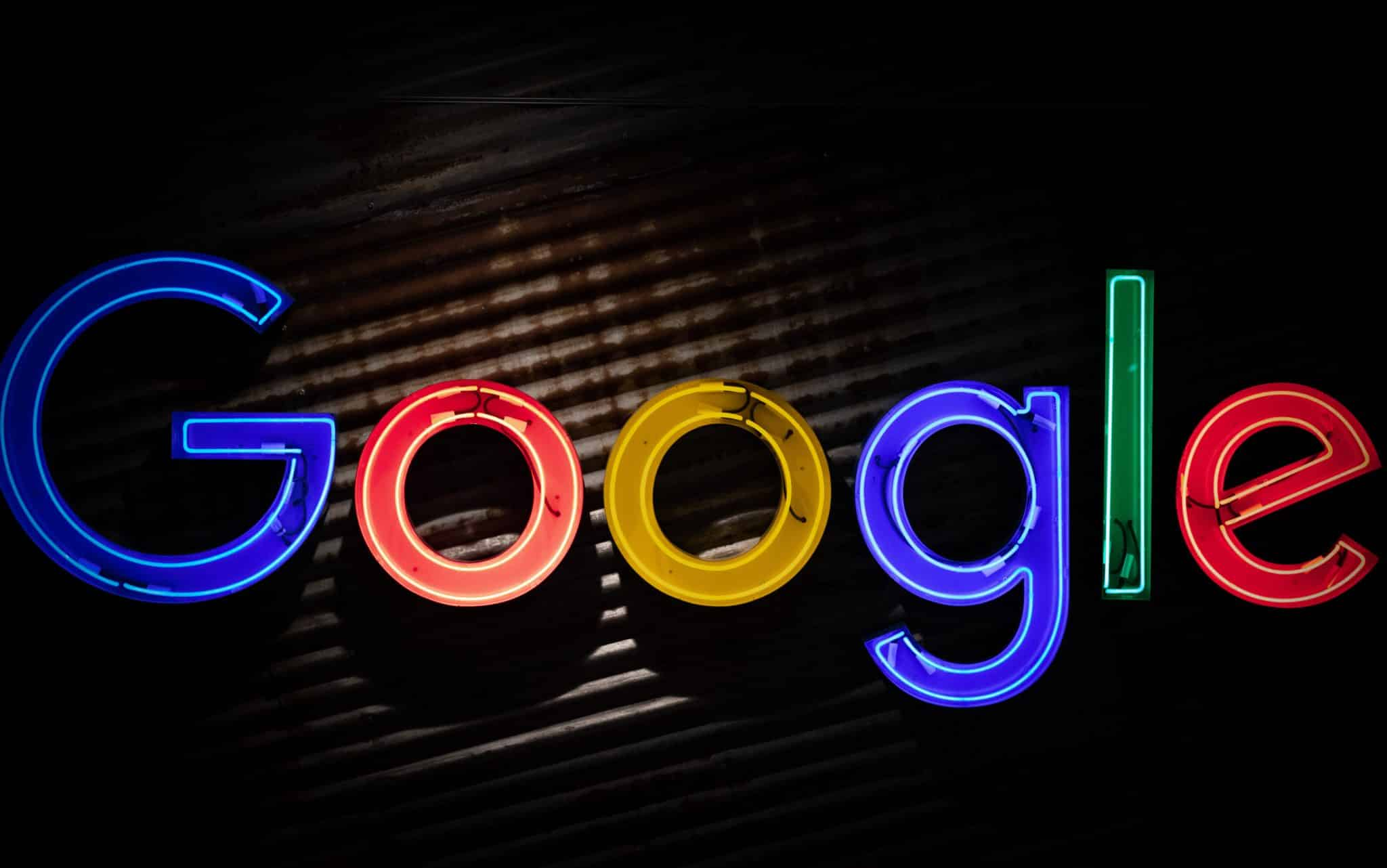 "A bright neon sign saying ""Google"" against a dark background"