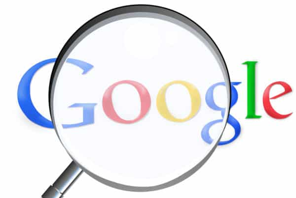 Google logo behind a magnifying glass.