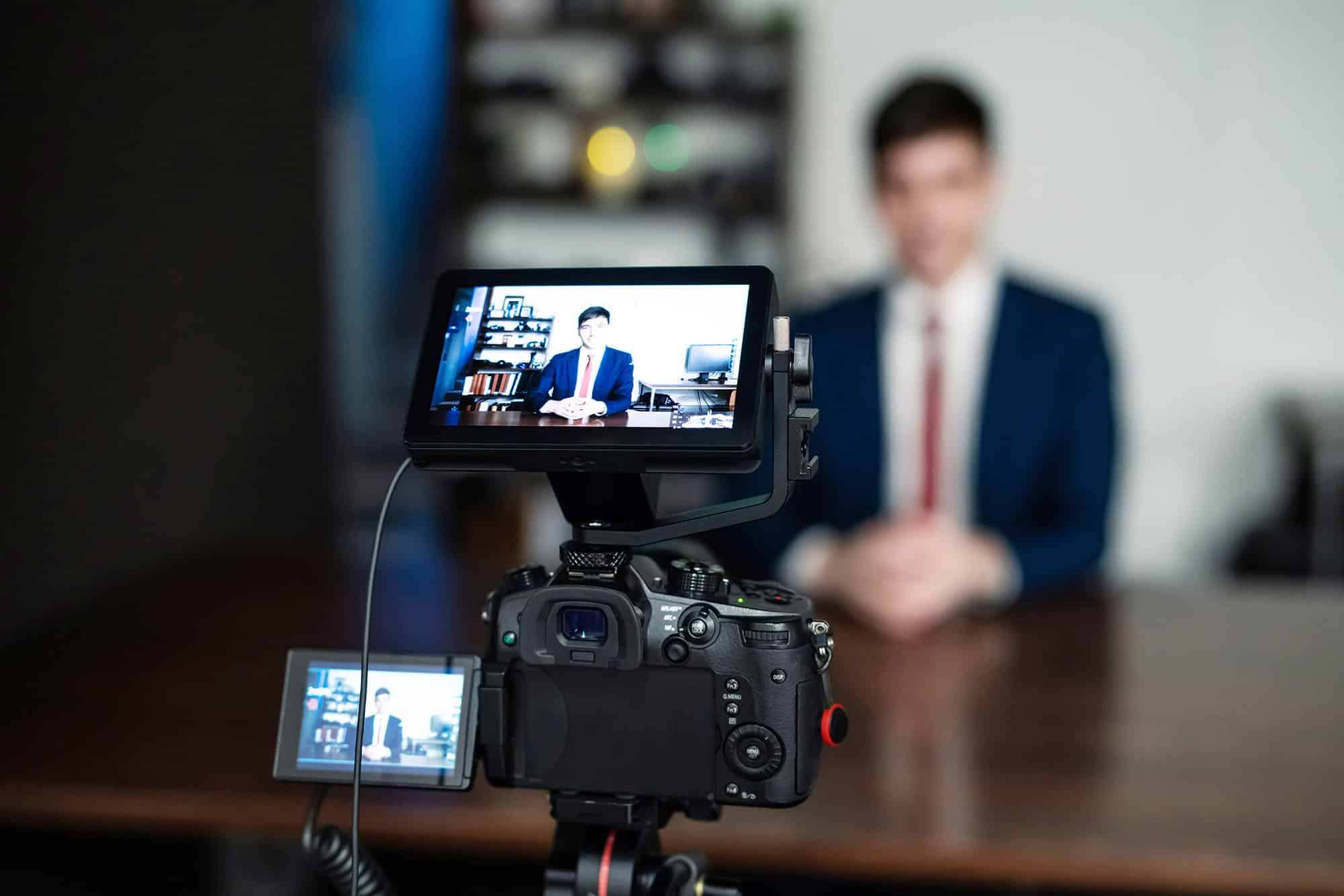 A man in a tie and suite speaking into a camera on a tripod. Social Eyes Marketing can help with all video production.