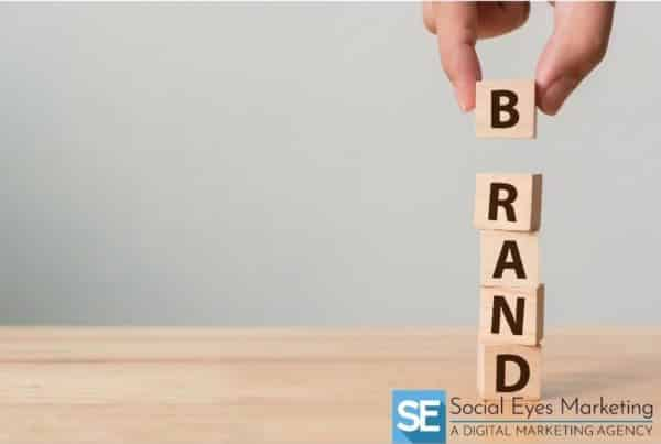 """A hand placing building blocks on top of one another to make the word """"brand"""""""