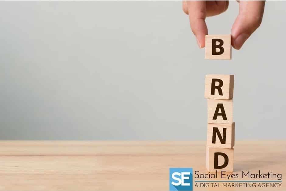 "A hand placing building blocks on top of one another to make the word ""brand"""