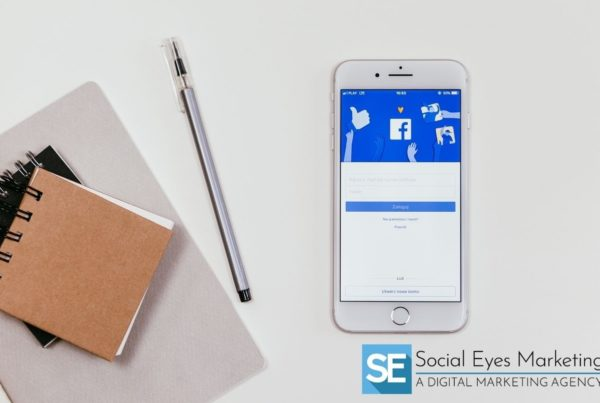 Facebook app open on a phone on a table with notepads