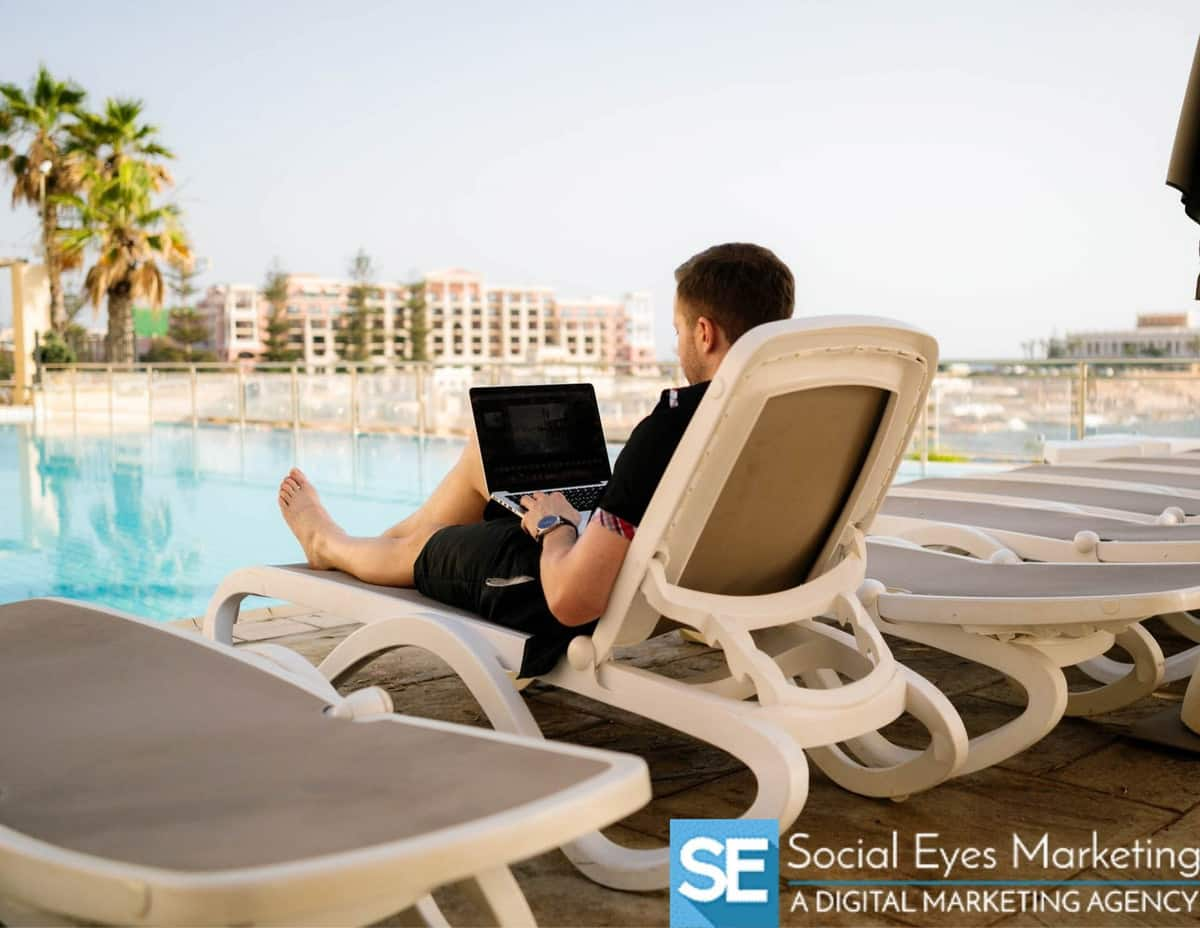A person sitting on a lounge chair next to a pool working on a computer.