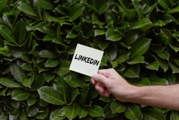 """Hand holding a post-it that says """"LinkedIn"""" with leaves in the background"""